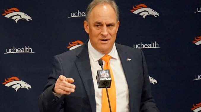 Vic Fangio in a black suit poses during an interview.