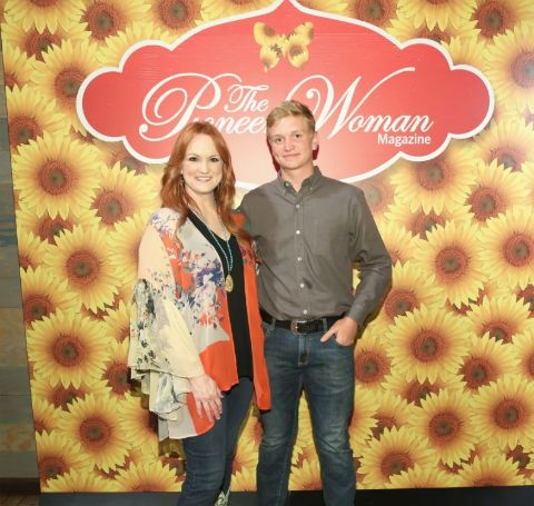 Bryce Drummond in grey shirt poses with famous mom Ree Drummond in The Pioneer Woman sets.