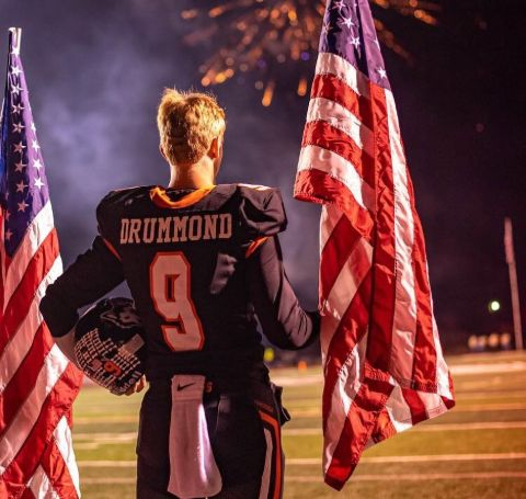 Bryce Drummond in the jersey of Pawhuska High School holds the national flag.