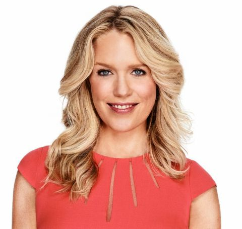 Jessica St.Clair  in a red outfit poses during a photoshoot.