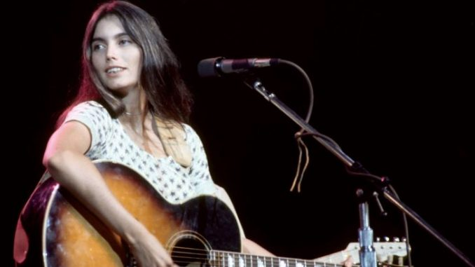 Emmylou Harris in white dress with guitar on hand singing at a stage.