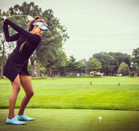 Seema Sadekar in a black outfit playing golf.