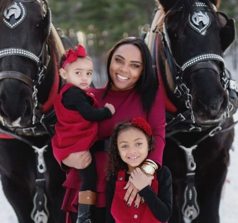 Shayanna  Jenkins in red dress poses with her two daughters.