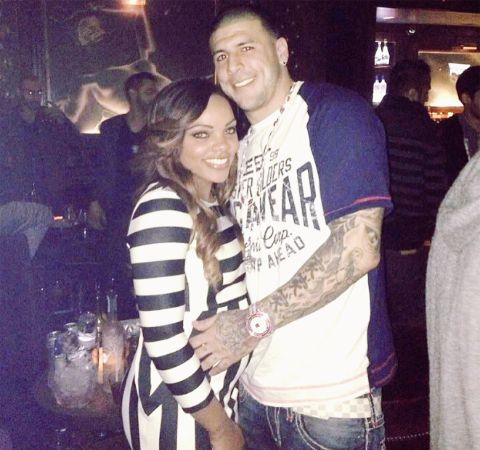 Shayanna  Jenkins in a black an white dress poses alongside NFL star Aaron Hernandez in a club.