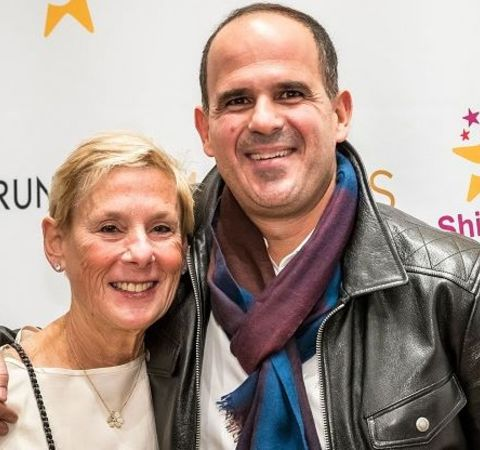 Roberto Raffel in a white dress poses with husband Marcus Lemonis in a black leather jacket.