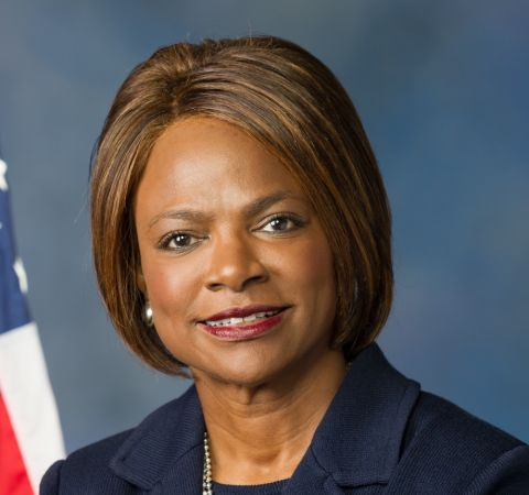 Val Demings in a black coat poses for a photoshoot.