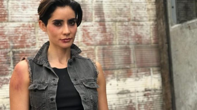 Paola Nunez in a black outfit poses during a photoshoot.