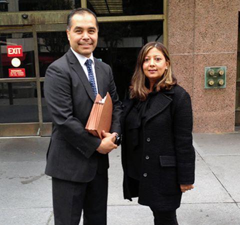 Minakshi Jafa-Bodden in a black dress on the right poses alongside fellow attorney.