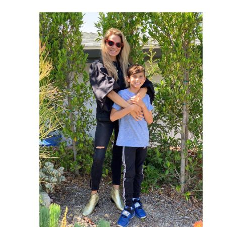 Cyia Batten on a black dress poses with her son.