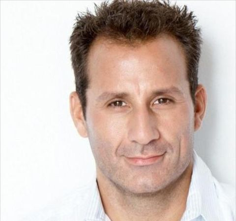 Michael Boisvert in a white shirt poses during a photoshoot.