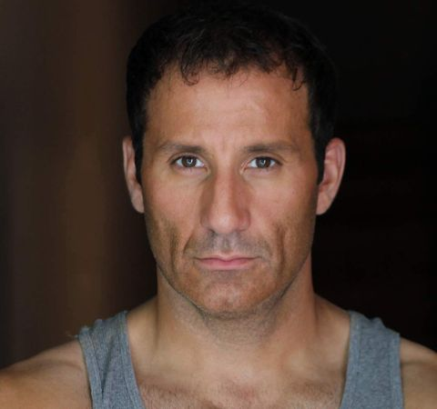Michael Boisvert in a grey vest poses for a photoshoot.