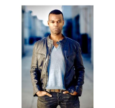 Demore Barnes in a black jacket and black pant poses during a photoshoot.