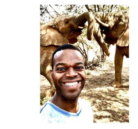Demore Barnes in a white t-shirt poses in front of animals.