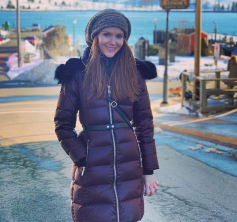 Darby Stanchfield in a brown jacket poses for a picture at Canada.