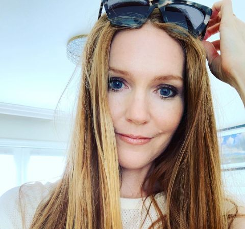 Darby Stanchfield in a white t-shirt poses a selfie.