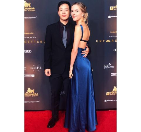 Kari Perdue in a blue dress poses alongside actor Hayden Szeto at an event.