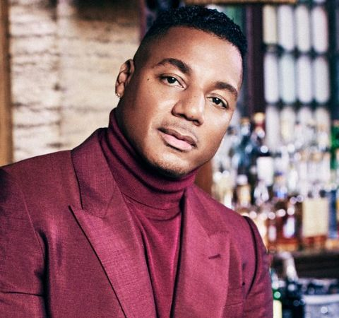 Rich Dollaz in a red suit poses for a photo.
