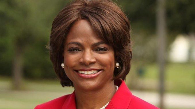Val Demings in a red coat poses for a picture.