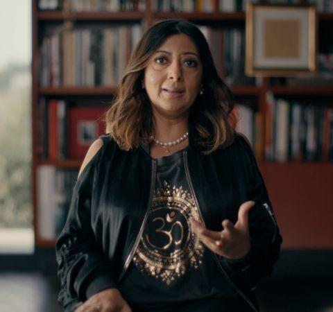 Minakshi Jafa-Bodden in a black dress caught on camera during an interview.