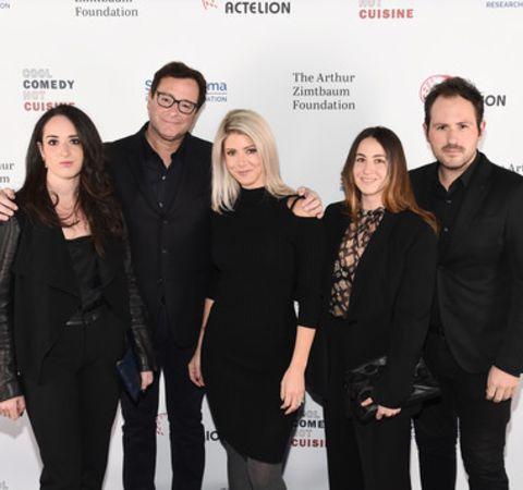 Lara Melanie Saget in a black dress poses alongside dad Bob Saget and sisters.