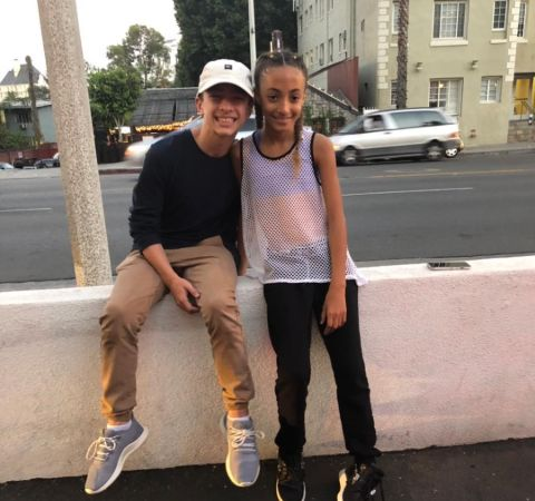 Jake Monreal in a black t-shirt poses with Sophia Pippen.