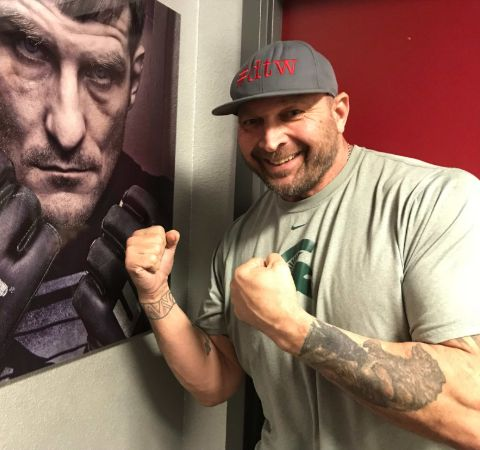 Tony Mandarich in a grey t-shirt poses beside a UFC poster.