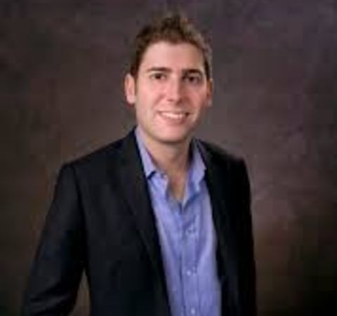 Eduardo Saverin  in a black suit poses for a picture.