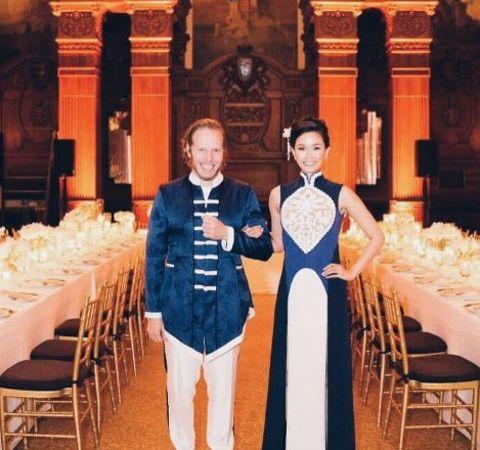 Rachel Kum in a white-blue dress poses alongside husband Alex Lloyd.
