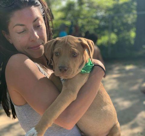 Renee Portnoy in a grey top hugs a dog.