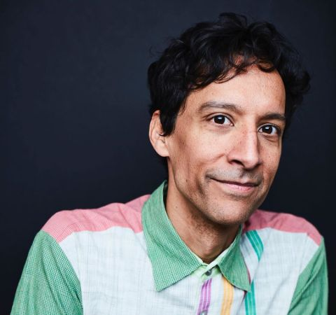 Comedian Danny Pudi in a green t-shirt poses for a picture.