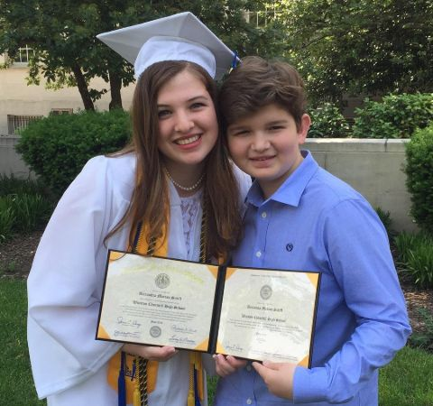 Alexa Schiff in a graduation down poses with her little brother.