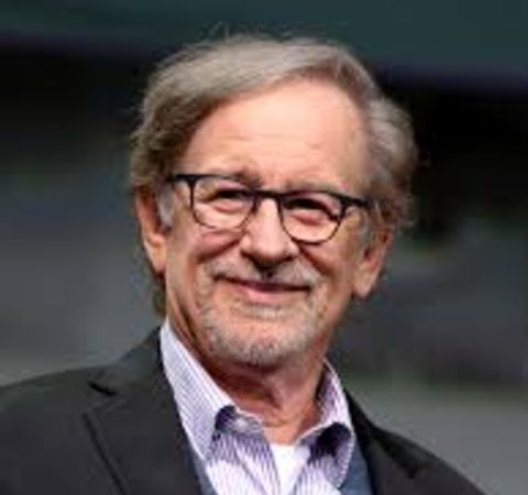 Steven Spielberg in a black suit  poses for a picture.