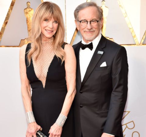 Kate Capshaw in black dress poses alongside Steven Spielberg in a tux.