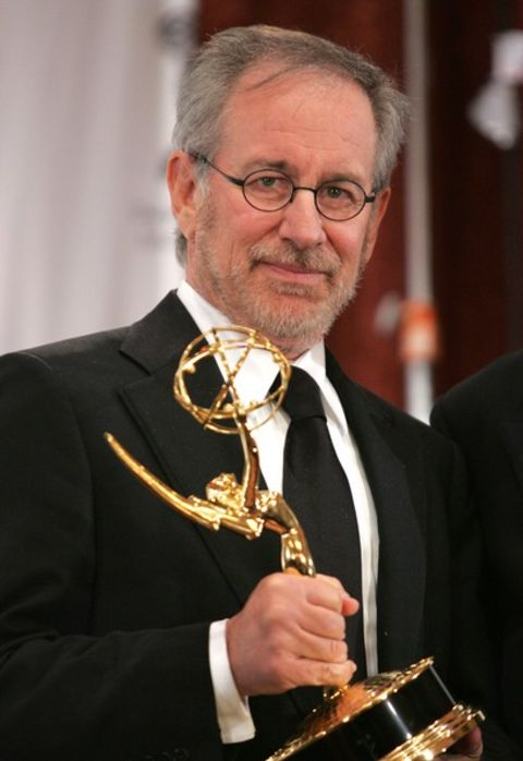 Steven Spielberg giving a pose while holding his Emmy Award.