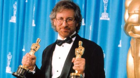 Steven Spielberg giving a pose holding his Oscars.