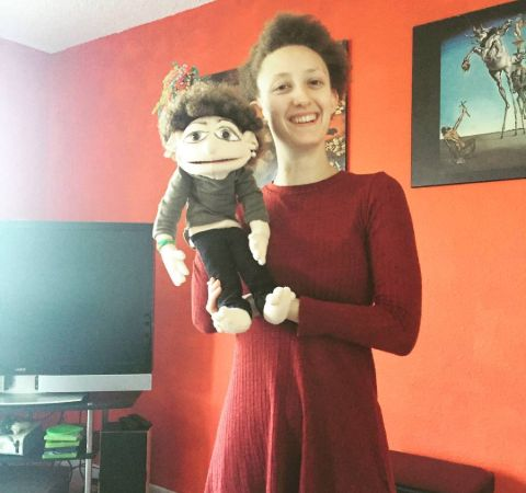 Maya Eshet in a red dress poses with a doll.