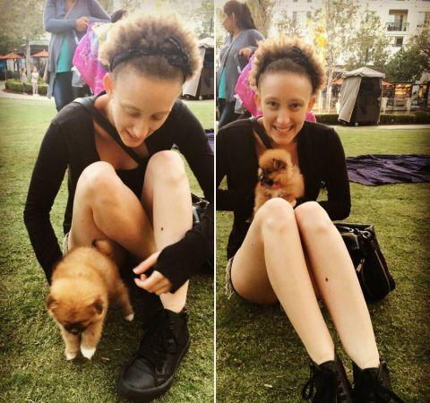 Maya Eshet  in a black dress with a puppy.