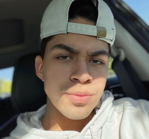 Niko Guardado in a white t-shirt and cap poses in a car.