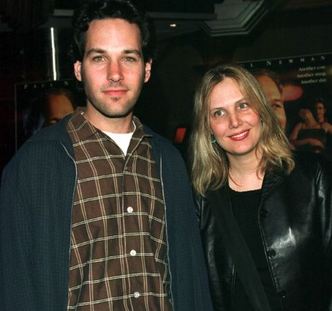 Julie Yaeger in a black t-shirt poses with husband Paul Rudd.