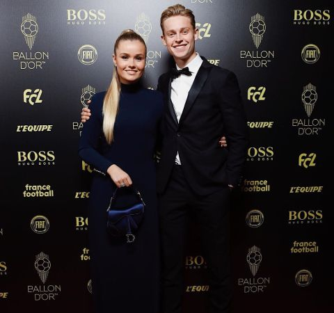 Mikky Kiemeney in a black dress poses with De Jong at an event.