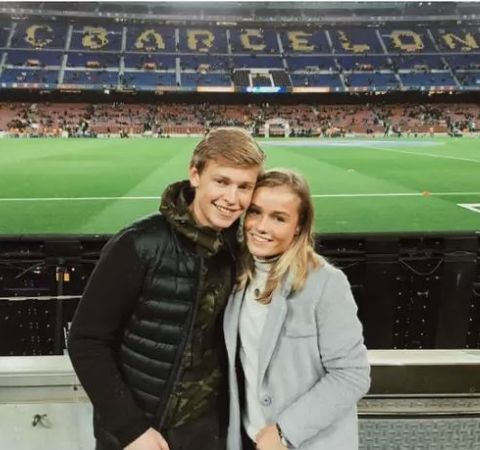Mikky Kiemeney in a black white coat poses with De Jong at Camp Nou.