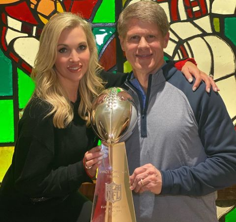 Tavia Hunt in a black dress poses with the super bowl trophy with husband Clark Hunt.
