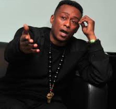 Professor Griff in a black suit poses for a picture.