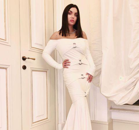 Elettra Lamborghini in a white gown poses for a picture.