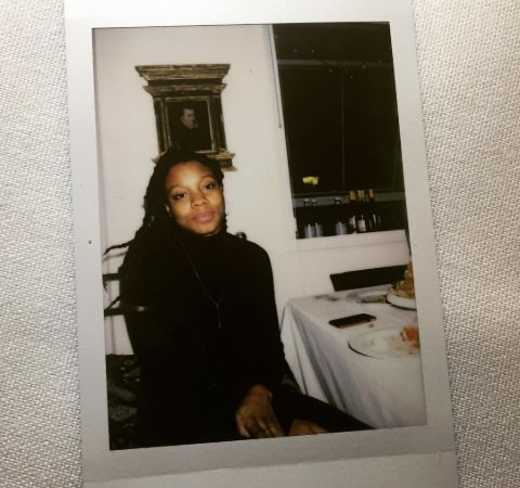 Nia DaCosta in a black dress poses for a picture.