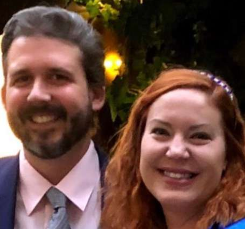 Rob Traegler in a black suit poses with his wife Amy Allen.