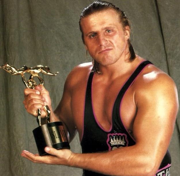 Owen Hart Holding An Award