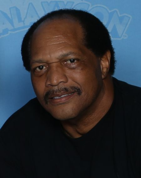 Ron Simmons in a black t-shirt poses for a picture.