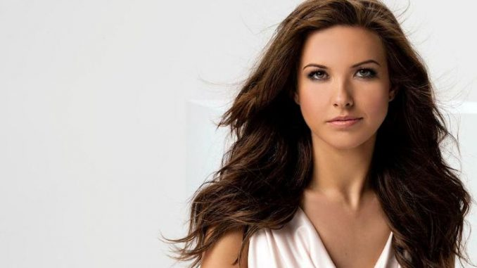 Audrina Patridge in a white top poses for a picture.