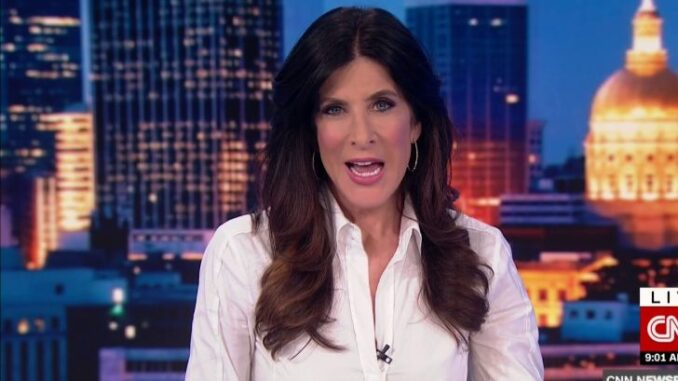 Natalie Allen in a white dress caught in the camera while anchoring the news..